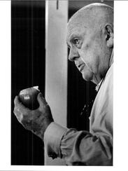 James Beard with an onion at a cooking demonstration.