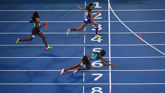 Shaunae Miller of the Bahamas, bottom, dives across the finish line to win gold in the 400 meters ahead of American Allyson Felix, top.