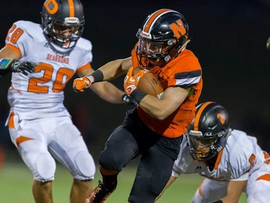 Northville's Nicholas Prystash (middle) finds an opening through the line of scrimmage against two Dearborn tacklers.