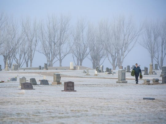 Fort Benton color guard member Russ Panthing looks for marked graves for the wreaths during the wreath laying ceremony at Riverside Cemetery.