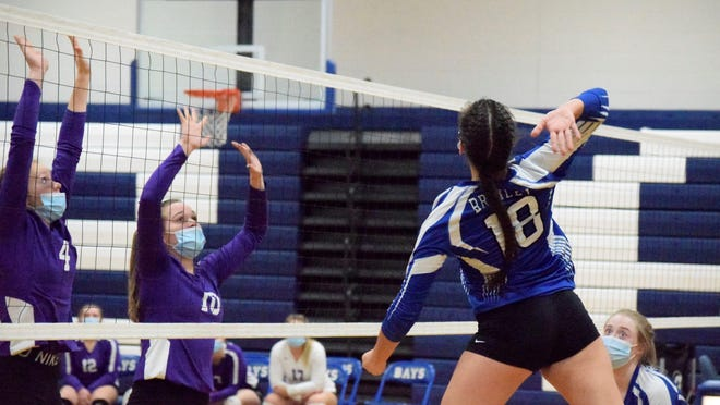 Lindsey Hill of Brimley (18) attacks against Pickford blockers Kennedy Guild (10) and Lucy Bennin (4) during an Eastern UP Conference volleyball match Tuesday night. The Panthers prevailed 3-1 over the Bays.