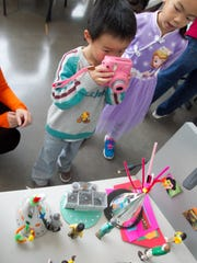 3-year-old Michael Liu takes an instant picture of