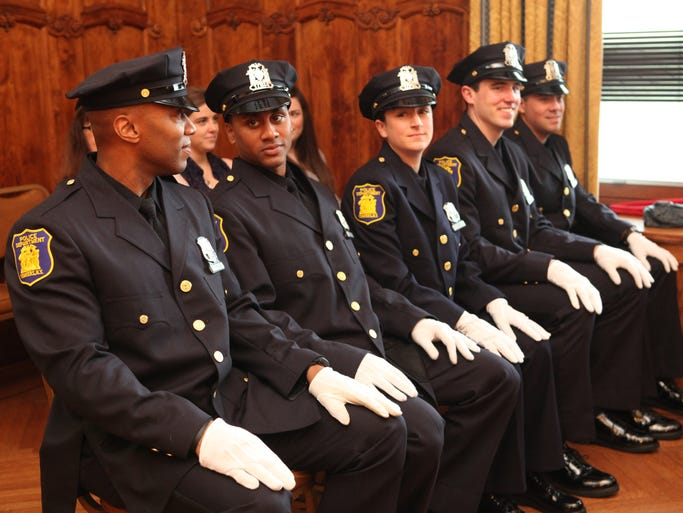 Police officers Hewitt DePass, 38, left, Neville Bennett, 29, Jessica Day, 29,  Robert Metz, 28, and Paul Bousche, 28, are being recognized at the Yonkers Police Department's recruit graduation ceremony, June 13, 2014 at Yonkers City Hall. The five recruits are part of the 137th class at the Westchester Police Academy. The academy is a 20 week program followed by a three week session in Yonkers.