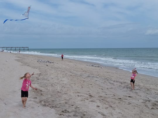 Kaley and Ryley Neal, both 5, daughters of Michelle and Adam L. Neal, fly a kite on the beach in 2016.