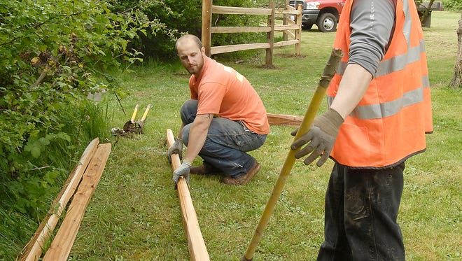 During Parks Appreciation Day in 2016, Colin Carter with Gig Harbor Public Works Department and Ben Coronado, with the Parks Commission, work together to build an extension to a split rail fence that was initially started during the previous year's Parks Appreciation Day at Wilkinson Farm Park.