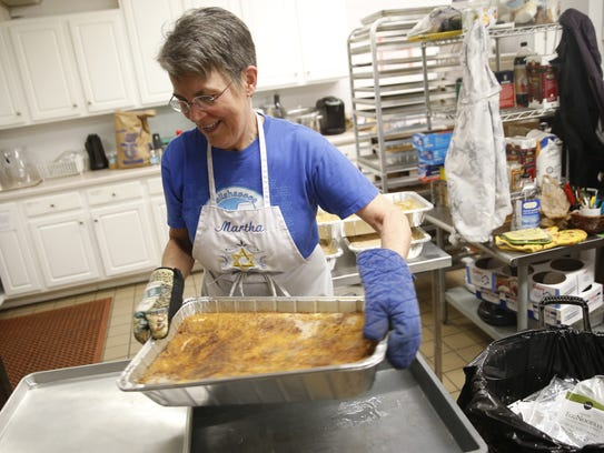 Martha Billings pulls a pan of Kugel out of the oven