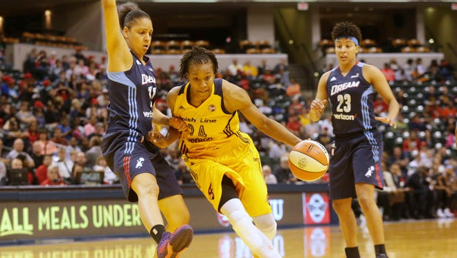 The Indiana Fever's Tamika Catchings dribbles past the Atlanta Dream's Cierra Burdick, left, and Layshia Clarendon, right, as the Indiana Fever play the Atlanta Dream at Bankers Life Fieldhouse, Friday May 20th, 2016. The Fever beat the Dream 94-85.