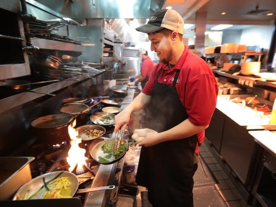 Austin Slinger cooks for the lunch crowd at Amerigo which celebrates it's 20th anniversary this week, and owner Ben Brock can measure the success of this classic Italian eatery by the loyalty of his repeat customers.