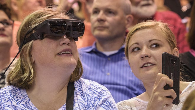 Mindi McDonald talks with her daughter, Delaney Sample, as she watches her son, Lucas Sample, receive his diploma at the SEP graduation ceremonies held May 29 at Drake University Knapp Center. McDonald is using a special set of glasses to be able to see her son graduate.