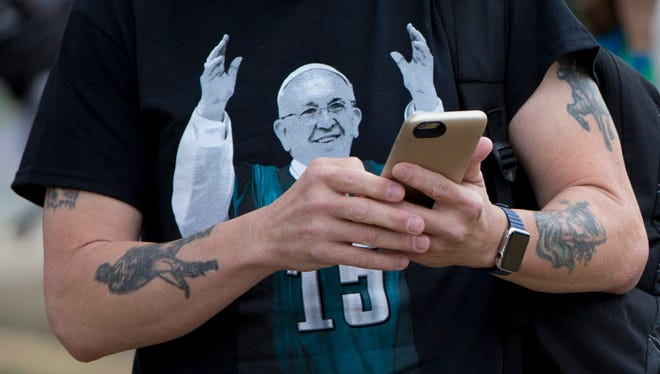 Bob Dreher of Doylestown, Pa., wears an image of Pope Francis on a Philadelphia Eagles T-shirt while working his smartphone before Pope Francis celebrates mass on Benjamin Franklin Parkway in Philadelphia on Sept. 27, 2015.