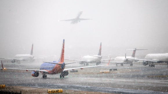 This file photo from Dec. 8, 2017, shows aircraft moving as snow falls at the Hartsfield-Jackson Atlanta International Airport.