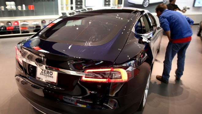 Tesla outsold other plug-in cars. Here, a customer looks at the Model S at a Tesla Motors showroom  at the Dadeland Mall in Miami