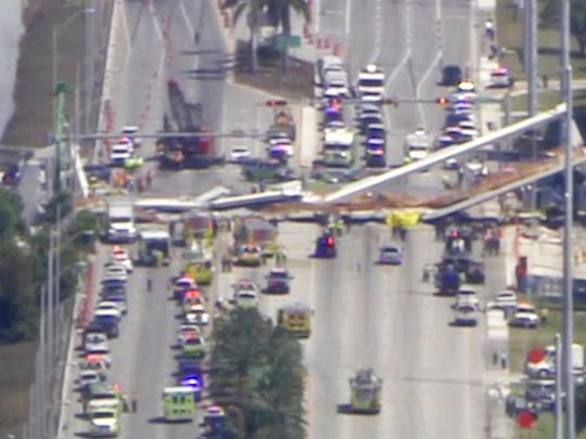 In this frame from video, emergency personnel work at the scene of a collapsed bridge in the Miami area, Thursday, March 15, 2018. (WPLG-TV via AP)