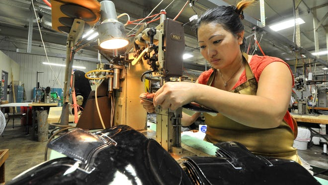 Shoua Xiong, of Wausau, performs gusset stitching on a shoe at the L. Jay Inc. facility in Wausau on Sept. 28, 2015.