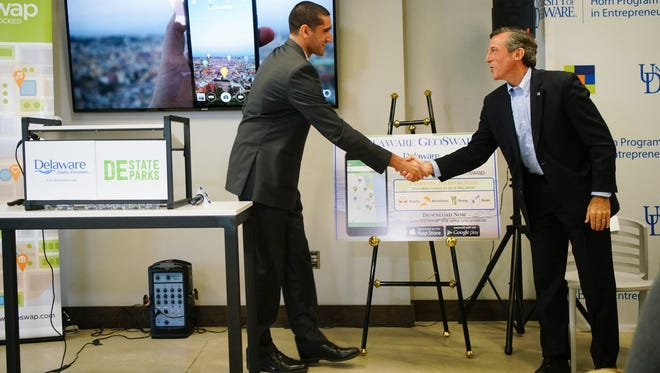 Jason Bamford shakes hands with Gov. John Carney after demonstrating the mobile app GeoSwap, that he and s classmates Jordan Gonzalez and Keith Doggett created at the University of Delaware's Horn Program in Entrepreneurship.