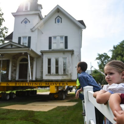 Children hang on a fence to watch as Wolfe House &