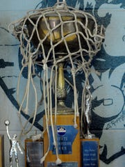 The Cotter Junior Warriors' 1965 state championship trophy, draped by a game net, remains a focal point in the school's trophy case at Cotter High.
