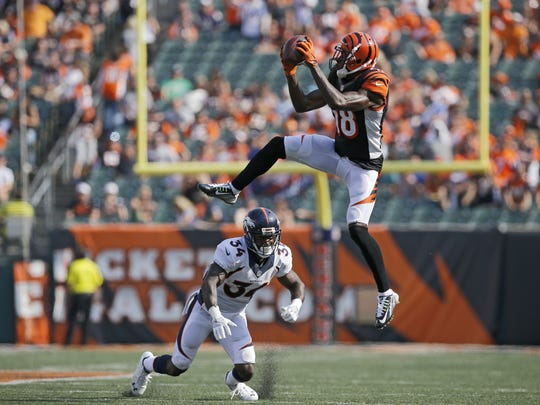 Cincinnati Bengals wide receiver A.J. Green (18) makes a leaping catch over Denver Broncos defensive back Will Parks (34) in the fourth quarter of the NFL Week 3 game between the Cincinnati Bengals and the Denver Broncos at Paul Brown Stadium on Sunday, Sept. 25, 2016. The Bengals fell to 1-2 with a 29-17 loss to the defending world champions.
