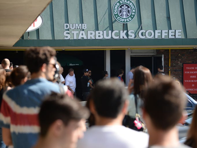 """People wait in a long line to get into a coffee shop named """"Dumb Starbucks"""" in the Los Feliz area of Los Angeles. The store resembles a Starbucks with a green awning and the Starbucks logo, but with the word """"Dumb"""" added before """"Starbucks.""""  All food and drink in the store is free."""