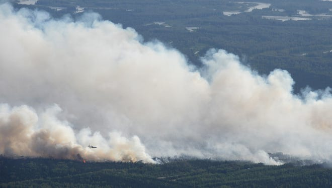 A State Division of Forestry air tanker works the Sockeye fire north of Kashwitna Lake  near Willow, Alaska. The wildfire north of Anchorage shut down a key highway and forced the evacuation of 1,700 homes after it mushroomed in size.