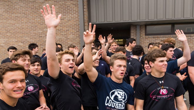 Members of the St. Thomas More football team cheer on their basketball counterparts as they board a bus to Lake Charles for the LHSAA Boy's Top 28 Semi-Finals in Lafayette March 9, 2016.