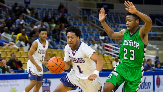 St. Thomas More's Jonathan Joseph drives against Bossier's Tyrese English during the play-off game in the LHSAA Boy's Top 28 Semi-Finals in Lake Charles March 10, 2016.