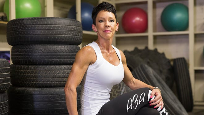 Bodybuilder Jessica Wright-Wiltz sits on tires she uses to train boot camp clients with at her gym in Lafayette July 7, 2016.