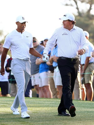 Tiger Woods and Phil Mickelson walk off the 10th tee box hand-in-hand during a practice round for the Masters golf tournament at Augusta National GC.