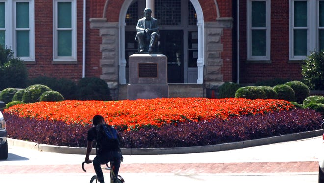 A bicycle rider goes by the Thomas Clemson sculpture in front of Tillman Hall at Clemson University.
