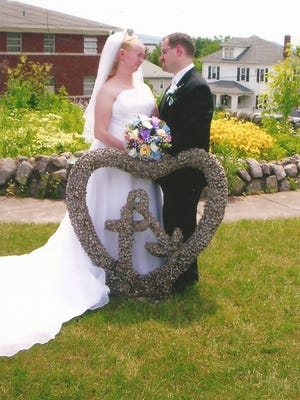 Shannon and Kevin Rakas take pictures near the Shrine behind St. Joseph's Church in Endicott after their wedding on June 24, 2006. They were married at St. James Church in Johnson City.
