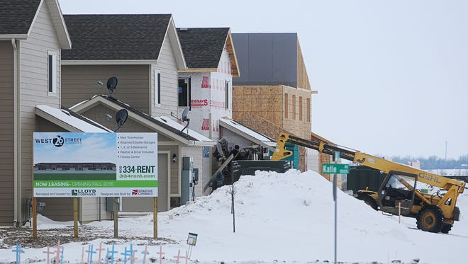 Construction workers work on an apartment building Tuesday, near the corner of West 26th Street and Katie Avenue in western Sioux Falls. A record 1,800 new housing units were built in 2015.