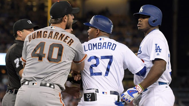 San Francisco Giants pitcher Madison Bumgarner (40) and Los Angeles Dodgers right fielder Yasiel Puig (66) are restrained by Dodgers first base coach first base coach George Lomgard (27) during a MLB game at Dodger Stadium.