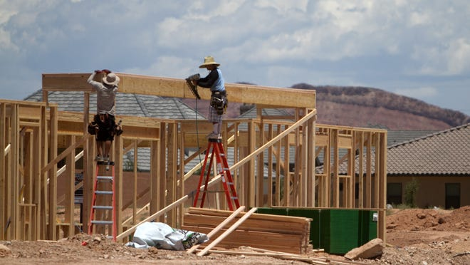 Workers frame a new house in the Little Valley area of St. George on June 30, 2014.