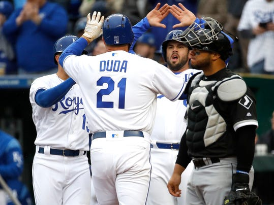 Chicago White Sox catcher Welington Castillo, right, stands at the plate while Kansas City Royals players celebrate a three-run home run by Lucas Duda during the first inning of a baseball game Thursday, March 29, 2018, in Kansas City, Mo. (AP Photo/Charlie Riedel)