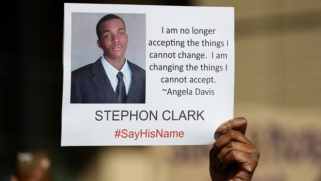 A protester holds a photo of Stephon Clark during a Black Lives Matter demonstration outside of Sacramento City Hall