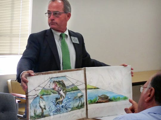 Lake Wichita Revitalization Committee Chairman Steve Garner holds an artist's rendering of a mural to be painted on the lake's spillway. The city of Wichita Falls has decided to enter into a services agreement with artist Ralph Stearns to move forward with the project.