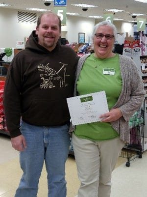 Sue Reich presents Tim Wiskow with a check for $1000.00 awarded by the ShopKo Foundation in appreciation for her hours of volunteer work in support of Whisper Hill Clydesdales Special Needs.