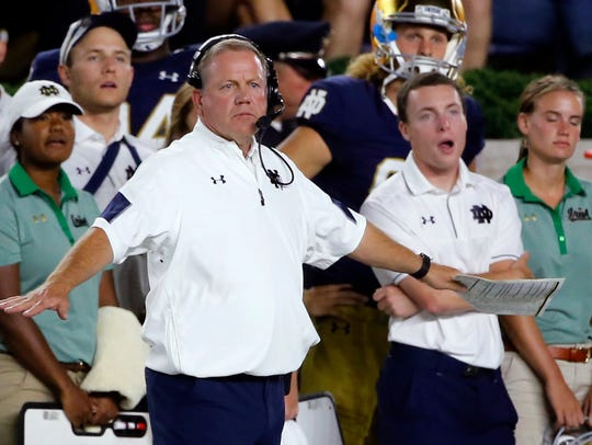 Notre Dame head coach Brian Kelly signals from the