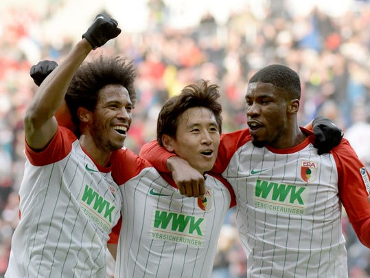From left: Augsburg's Caiuby scorer Koo Ja-cheol and Kevin Danso celebrate the opening goal during the German Bundesliga soccer match between FC Augsburg and Eintracht Frankfurt, in Augsburg, Germany, Sunday, Feb. 4, 2018. (Stefan Puchner/dpa via AP)