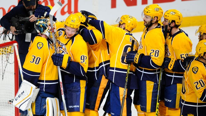 Nashville Predators goalie Carter Hutton (30) is congratulated by center Ryan Johansen (92) and teammates after a shut out against the Minnesota Wild at Bridgestone Arena.
