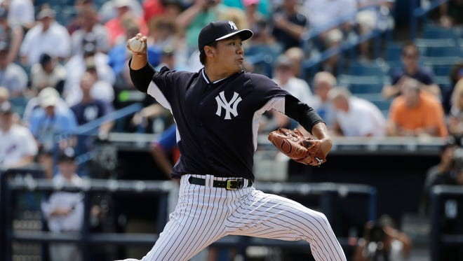 Yankees starting pitcher Masahiro Tanaka throws against the Mets in Tampa, Fla. during spring training. Despite having torn a ligament in his elbow last season, Tanaka says he has pitched without pain this spring.