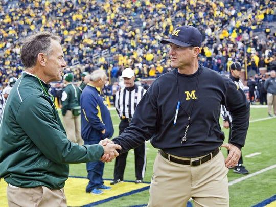 Michigan State coach Mark Dantonio, left, shakes hands