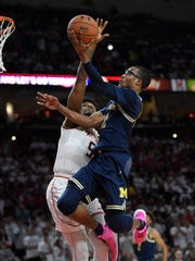 Michigan guard Muhammad-Ali Abdur-Rahkman goes to the