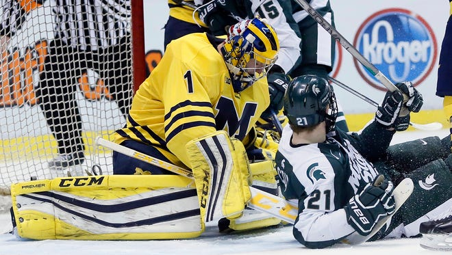 Michigan goalie Steve Racine (1) stops a shot against Michigan State's Mackenzie MacEachern (15) on Feb. 5, 2016, in Detroit.