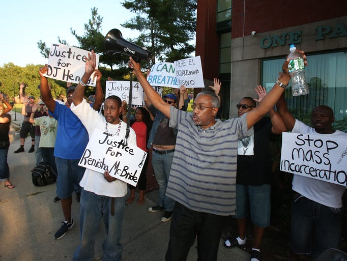 "Darrell Davis, with megaphone, leads the crowd in a chant of ""hands up, don't shoot"" during a demonstration outside Senator Charles Schumer's office in Peekskill Aug. 20, 2014. A group gathered to protest the police shooting in Ferguson, Missouri."