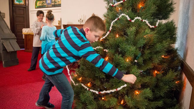 Sam Behrendt, 8, decorates an old-fashioned tree with handmade decorations at The Church at Crossroads in Daleville. The church, while not used regularly anymore, has a special candlelight Christmas Eve service starting at 10 p.m.