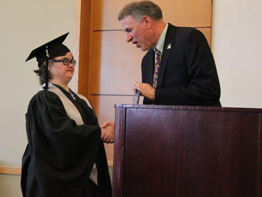 Natasha Price shakes the hand of the University of Nevada, Reno's Dean of Education Kenneth Coll