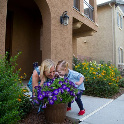 Kristin Seed and her daughter Sloane smell flowers