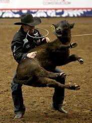 Trevor Brazile of Decatur, TX takes down his calf during
