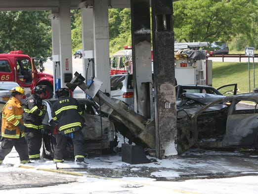 White Plains firefighters and Westchester county police work at the scene of an accident and fire in the Mobil station on the Hutchinson River Parkway in White Plains June 3, 2014.